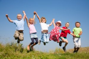 Group happy children jumping on summer meadow against blue sky